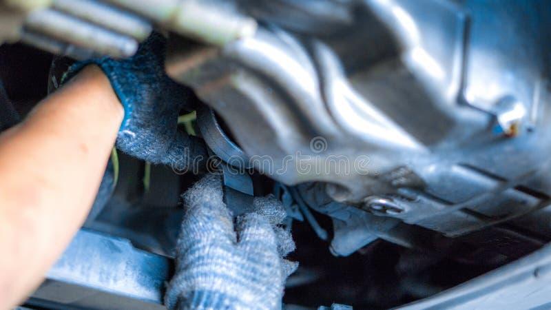 Закрыть механическую руку с заменой моторного фильтра в гараже автомобиля и копировальных помещениях, использовать для техническо стоковое фото rf