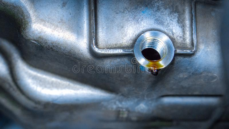 Закрыть систему нефтяного стока с заменой моторного масла в гараже автомобиля и копировальных помещениях, использовать для обслуж стоковые фотографии rf
