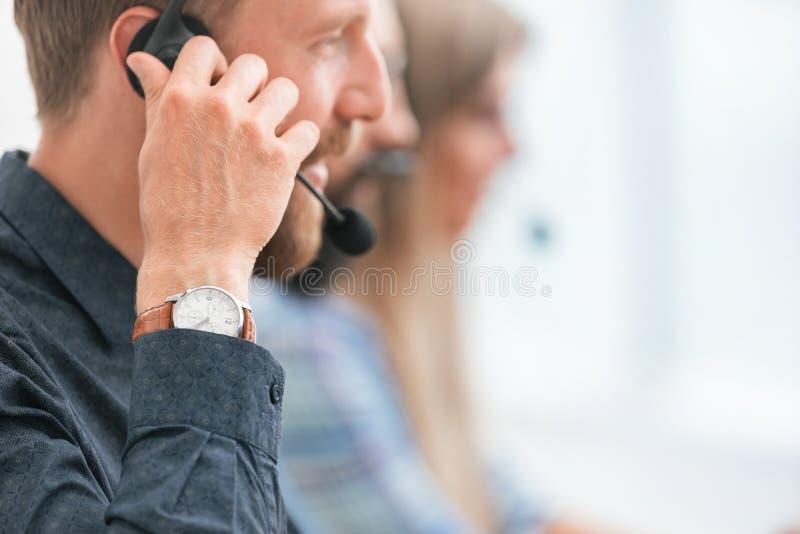 Закрыть улыбающийся сотрудник центра обработки звонков смотрит на тебя стоковое фото