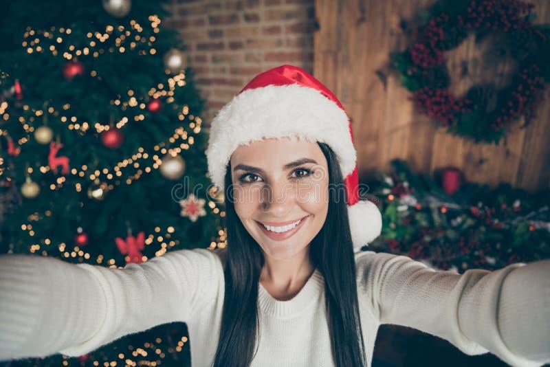 Закрыть фото позитивной радостной девушки наслаждаться рождественские каникулы сделать селфи носить santa clus головной у дома стоковое фото