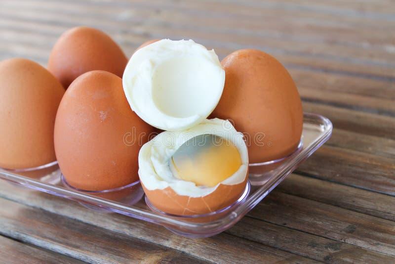 закрыть шесть коричневых яиц в пластиковой коробке на бамбуковом столе с одним разбитым вареным яйцом, вид сверху стоковые фотографии rf
