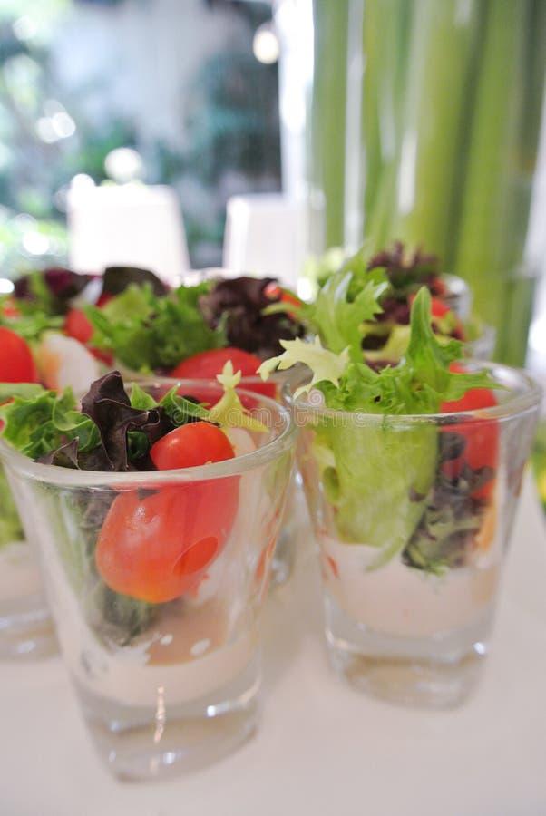Закуска, мини зеленый салат и томат в малом стекле стоковые изображения
