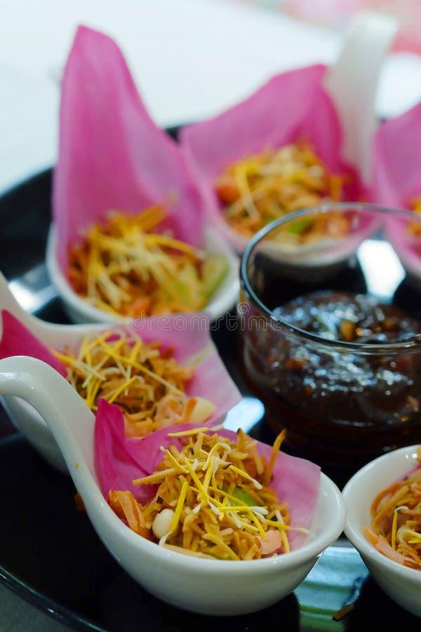 Закуска Таиланда ` Bua kleeb Meung Kum ` традиционная делает смешиванием кокоса Roasted при много тайскую траву оборачивая с розо стоковые изображения rf