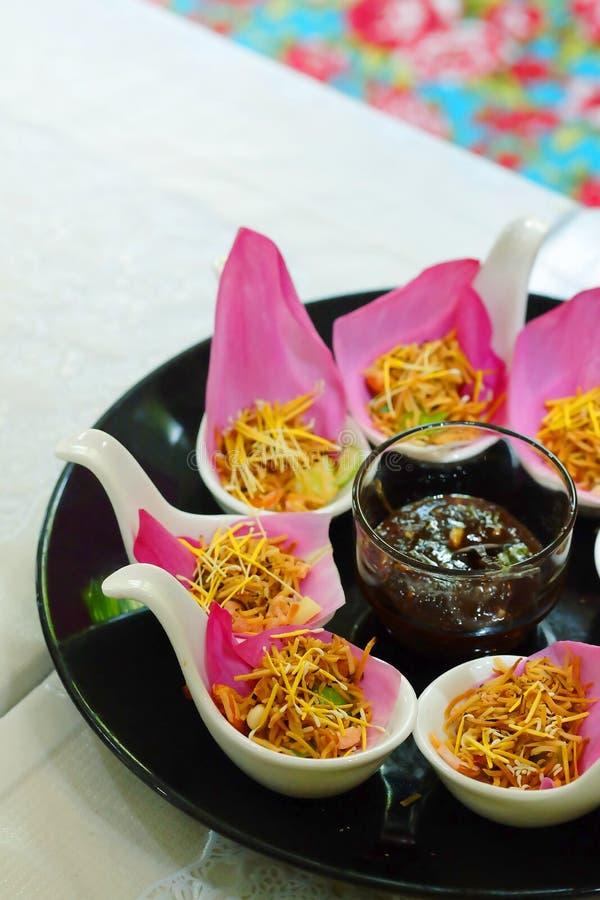 Закуска Таиланда ` Bua kleeb Meung Kum ` традиционная делает смешиванием кокоса Roasted при много тайскую траву оборачивая с розо стоковое фото rf