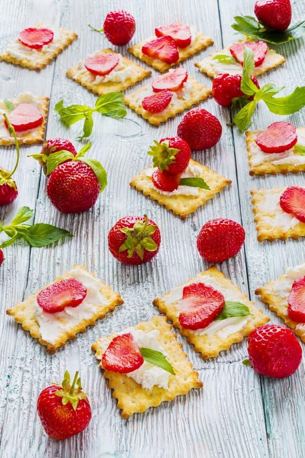 Закуска: шутихи с плавленым сыром, свежими клубниками и листьями мяты на светлой деревянной предпосылке стоковое изображение rf