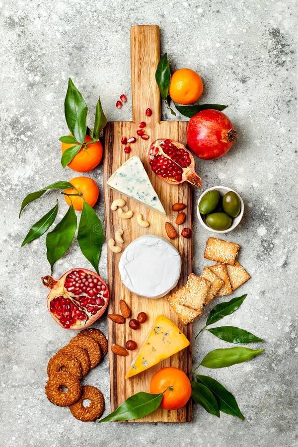 Закуски ставят на обсуждение с закусками antipasti Доска разнообразия сыра над серой конкретной предпосылкой Взгляд сверху, плоск стоковая фотография rf