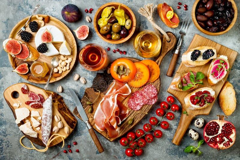 Закуски ставят на обсуждение с итальянскими закусками и вином antipasti в стеклах Установленные Brushetta или подлинные традицион стоковое фото rf