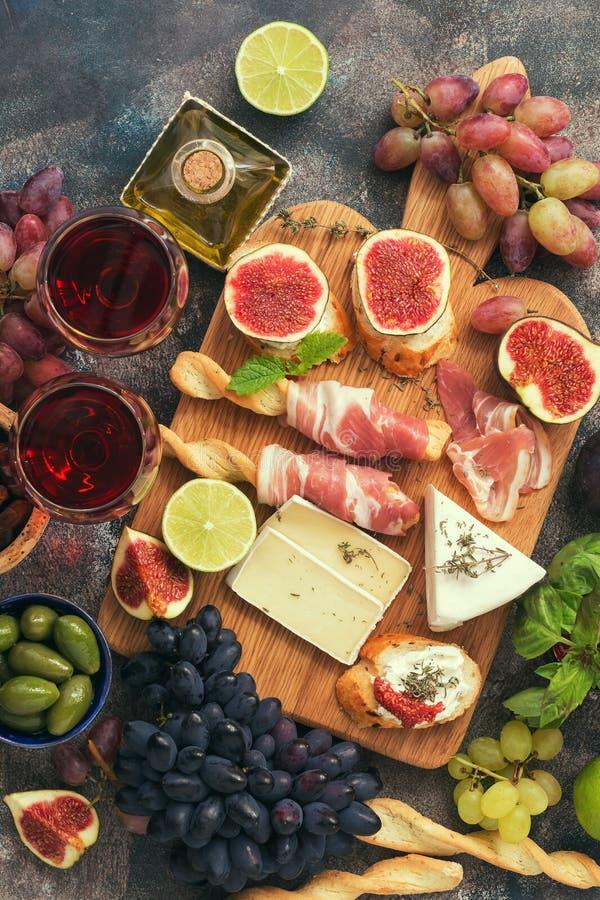 Закуски ставят на обсуждение с итальянскими закусками и вином antipasti в стеклах Традиционное grissini ручек итальянского хлеба  стоковые фотографии rf