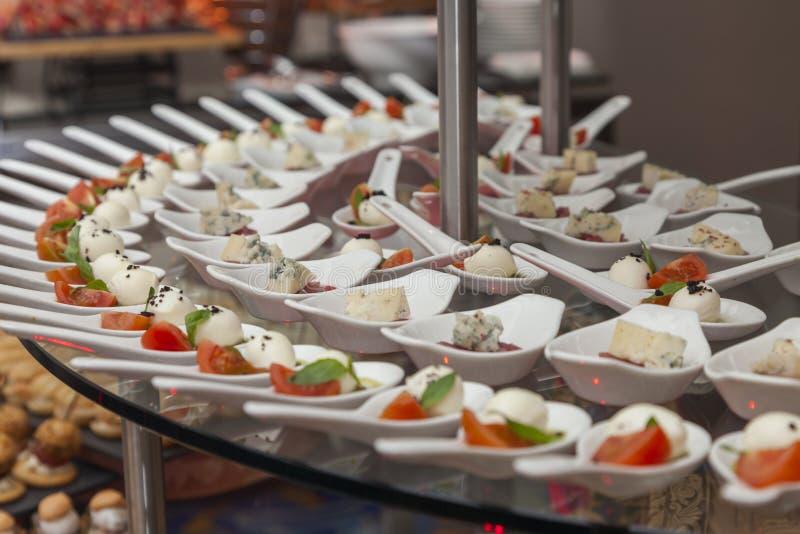 Закуски с томатом и моццареллой на ложке стоковая фотография rf