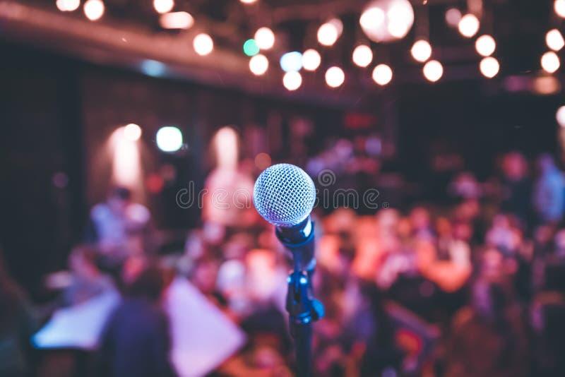 Зала события: Закройте вверх стойки микрофона, мест с аудиторией в расплывчатой предпосылке стоковые фото