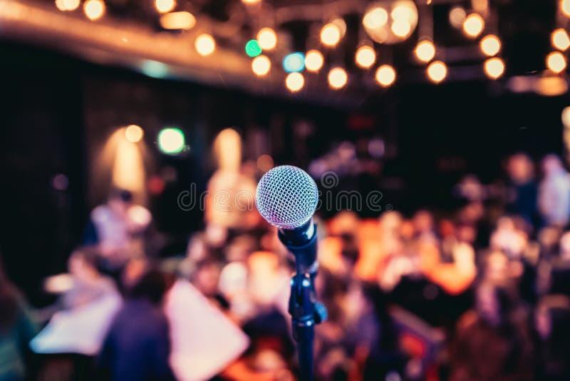 Зала события: Закройте вверх стойки микрофона, мест с аудиторией в расплывчатой предпосылке стоковые изображения