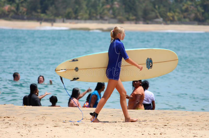 ЗАЛИВ YARUGAM, 12-ОЕ АВГУСТА: Маленькая девочка идет заниматься серфингом стоковое фото