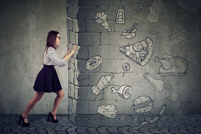 Заманчивость мотивированной женщины сопротивляясь еды быстрой ноги и выбирать лучшую диету стоковая фотография