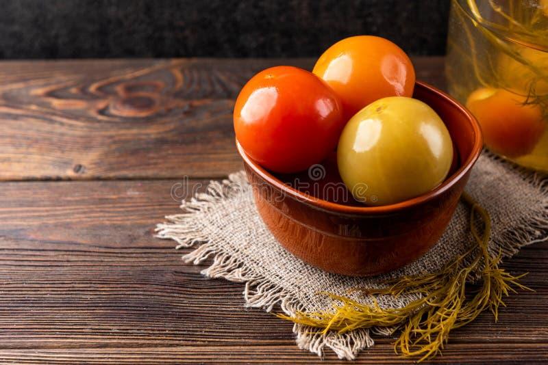 Замаринованные томаты на деревянной предпосылке стоковое фото rf