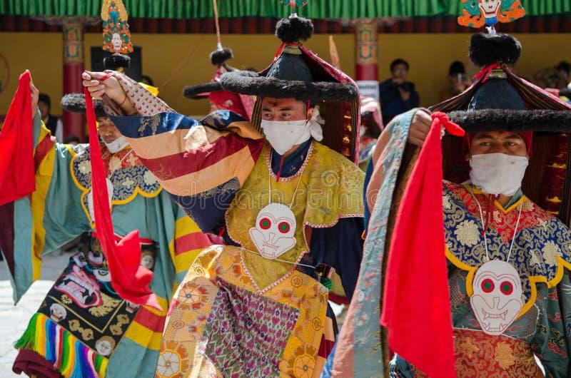 Замаскированные танцоры в традиционном Ladakhi костюмируют выполнять во время ежегодного фестиваля Hemis стоковое фото