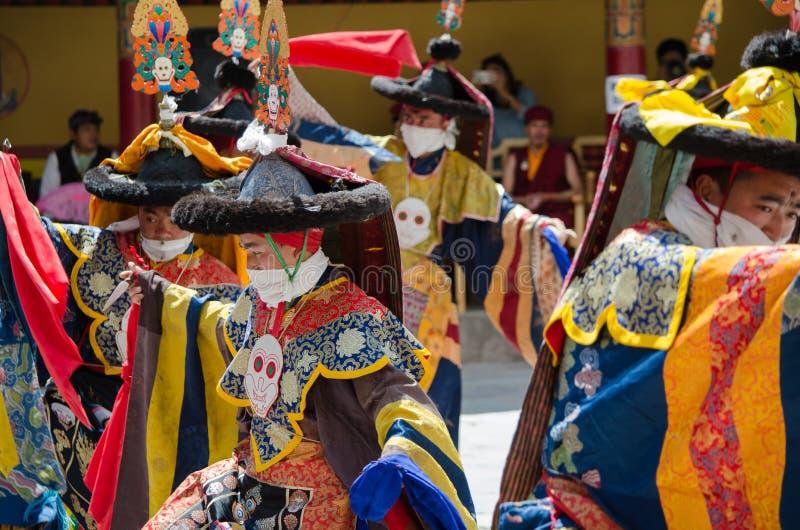 Замаскированные танцоры в традиционном Ladakhi костюмируют выполнять во время ежегодного фестиваля Hemis стоковое фото rf