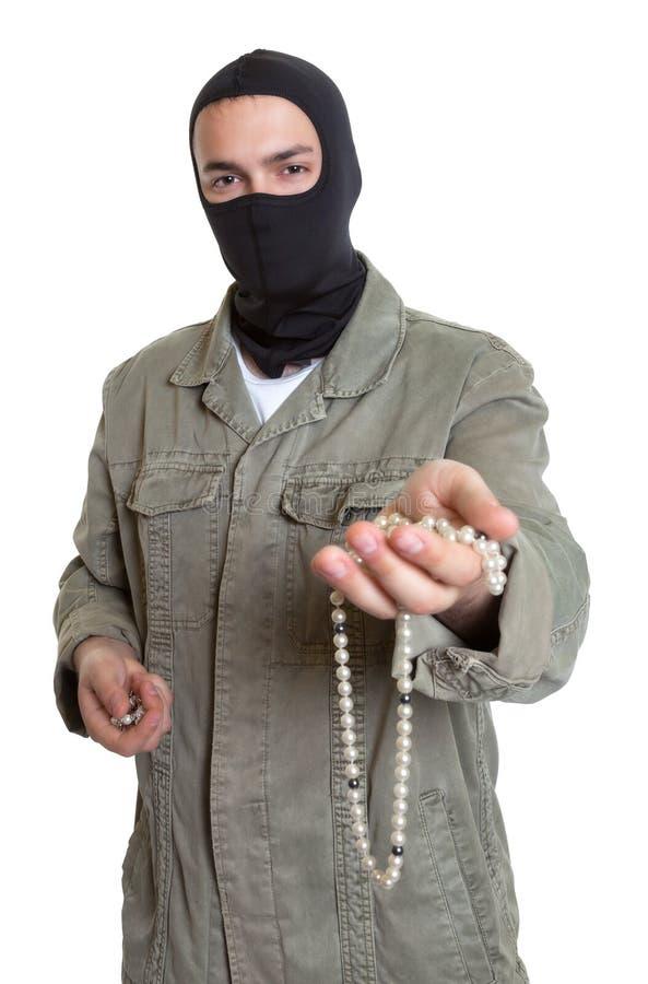 Замаскированный взломщик показывая ювелирные изделия стоковые фото
