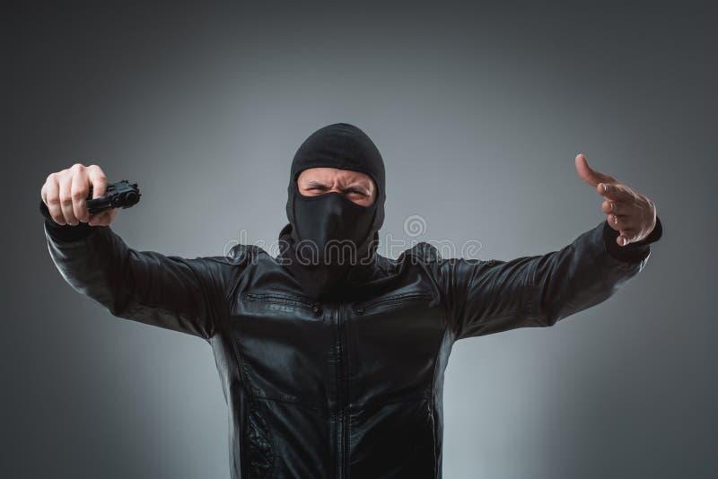 Замаскированный разбойник при оружие, смотря в камеру стоковое изображение