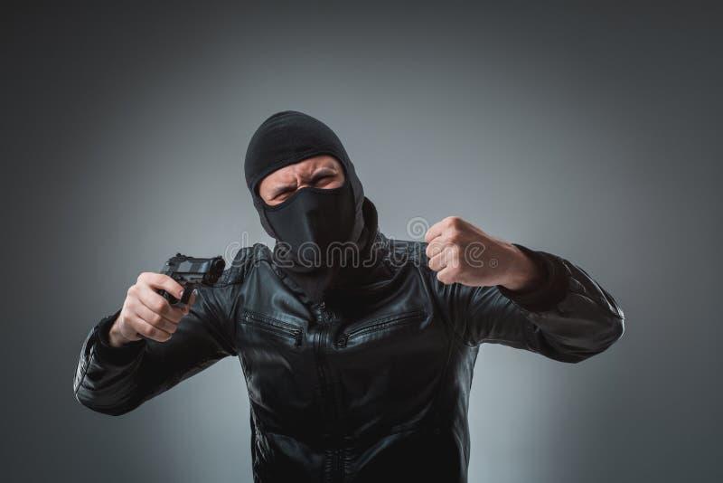 Замаскированный разбойник при оружие, смотря в камеру стоковые фотографии rf