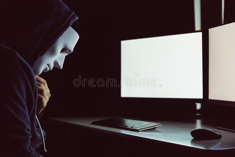 Замаскированный хакер под клобуком используя компьютер, который нужно прорубить в систему и пробовать совершить преступление в ко стоковые изображения