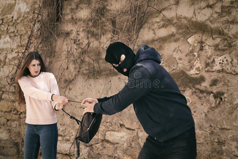 Замаскированный человек пробуя украсть рюкзак женщины Уголовное преступление стоковые фотографии rf