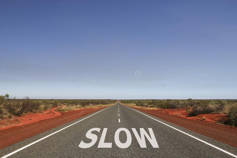 ЗАМЕДЛЯЙТЕ написанный на дороге стоковое изображение rf