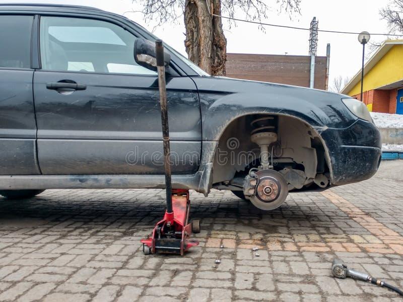 Замена колеса на пункте обслуживания автошины Автомобиль без колеса поднятого на поднимает домкратом стоковое изображение