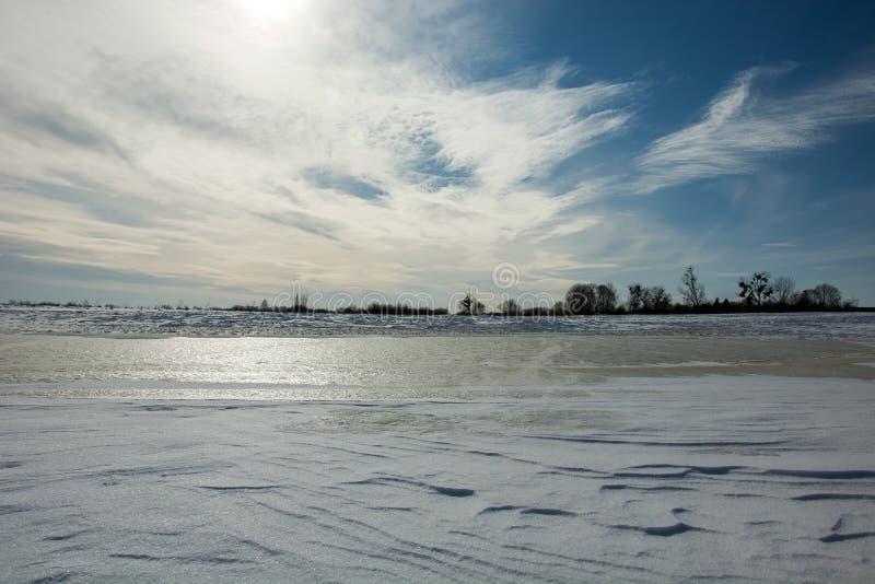 Замерли вода, снег в поле в солнечности стоковые изображения rf