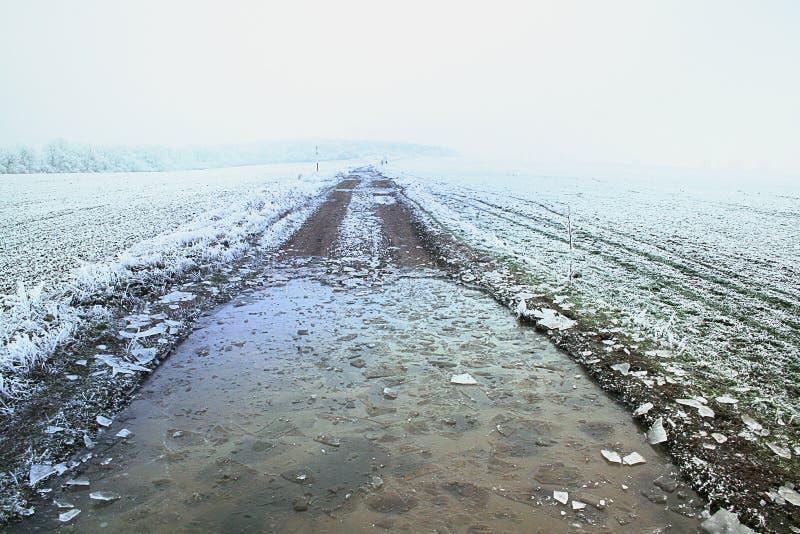 Замерли зимой, который дорога поля с треснутым льдом стоковое изображение