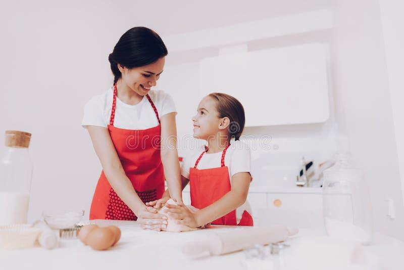 Замешайте тесто с мамой Маленькая девочка и тесто стоковое изображение rf