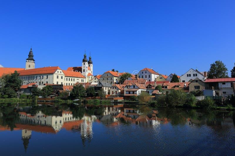 Замок сказки и старый городок с красивыми отражениями зеркала берега озера на ровной воде под голубым солнечным небом в Telc стоковое изображение