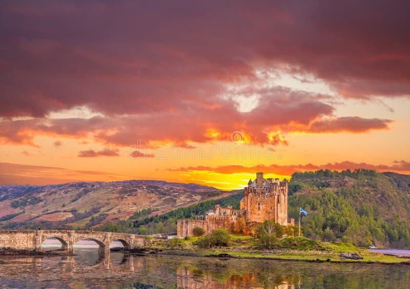 Замок Eilean Donan против захода солнца в гористых местностях Шотландии стоковое изображение rf