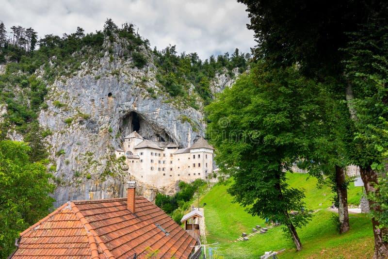 Замок Predjama, Словения Сценарный взгляд замка Predjama около рта пещеры Postojna Архитектура Anciend builded в утесе старо стоковое изображение rf