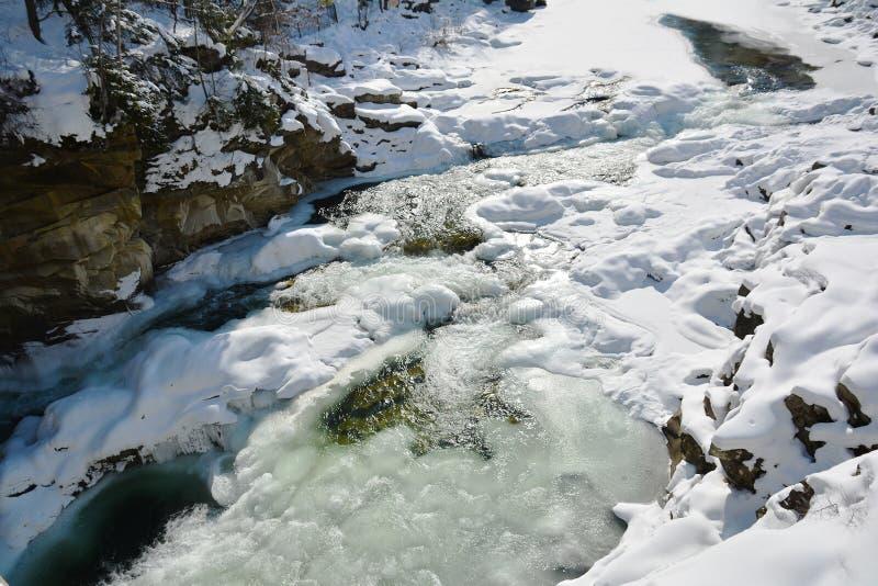 Замороженное быстрое река горы в зиме Плавить весны льда, spr стоковые изображения
