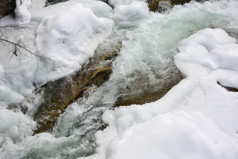 Замороженное быстрое река горы в зиме Плавить весны льда, spr стоковые фотографии rf