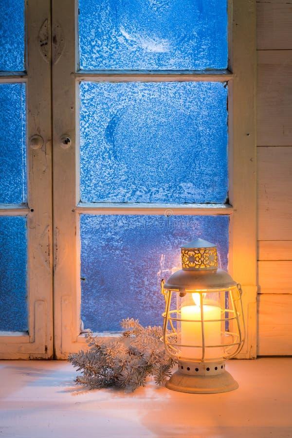 Замороженное голубое окно с свечой для рождества стоковое изображение