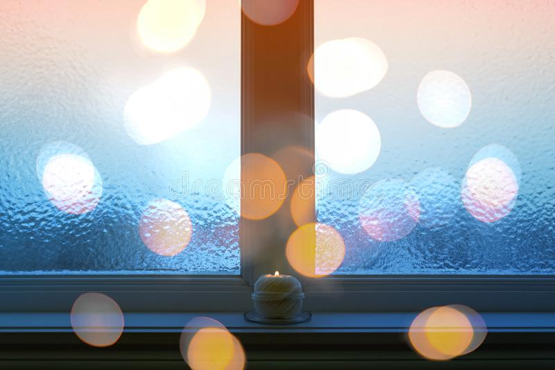 Замороженное окно, света bokeh, и горя свеча стоковые фотографии rf