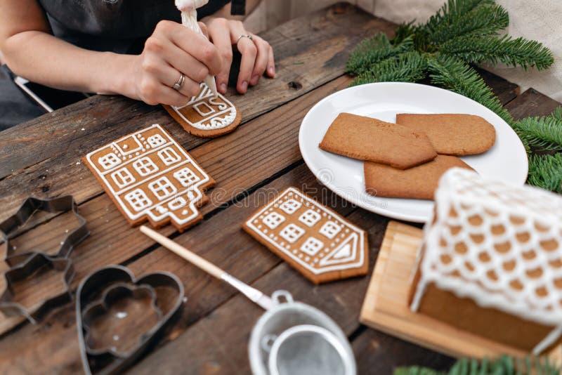 Замороженность пекарни рождества Женщина украшая печенья пряника меда на деревянной коричневой таблице Крупный план, космос экзем стоковые фотографии rf