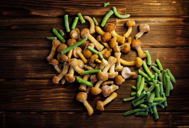 Замороженные дикие грибы и зеленые фасоли на деревянном острословии предпосылки стоковая фотография rf