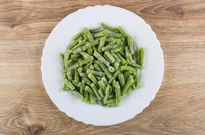 Замороженные зеленые фасоли в белом блюде на деревянном столе стоковые изображения rf