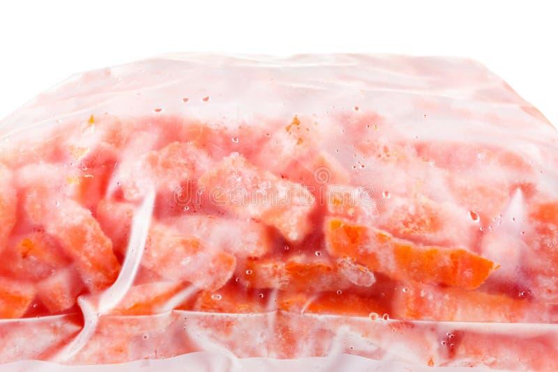 Замороженные моркови в полиэтиленовом пакете, изолированном на белизне стоковые фото