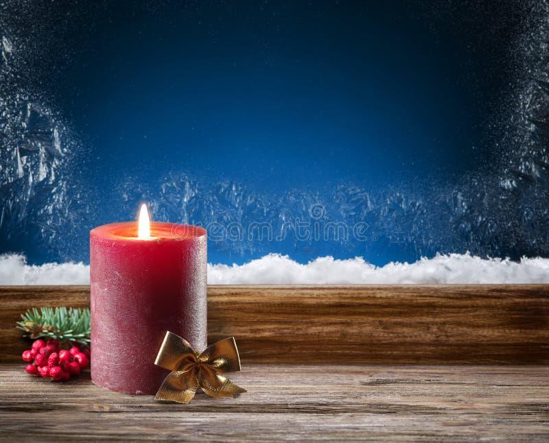 Замороженные окно и свеча горения в ноче стоковое фото rf