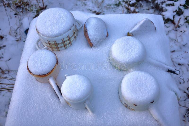 Замороженные старые ржавые сотейники литейного металла на таблице под снегом во время зимы стоковые изображения
