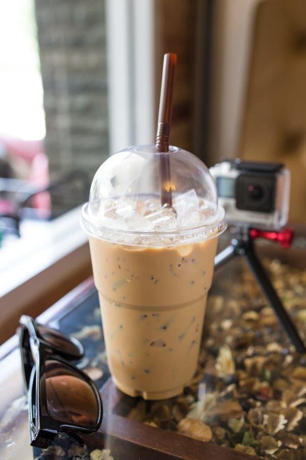 замороженные эспрессо, sunglass и предпосылка камеры стоковые фото