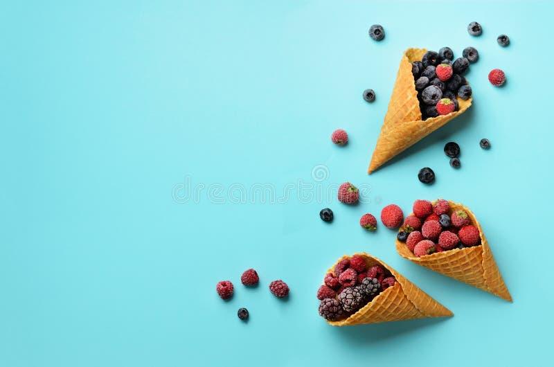 Замороженные ягоды - клубника, голубика, ежевика, поленика в конусах waffle на голубой предпосылке Взгляд сверху знамена стоковая фотография rf