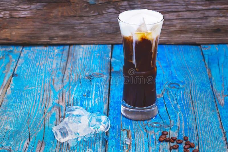 Замороженный кофе с взбитым мороженым молока и карамельки в высокорослых стеклах на деревенском деревянном столе стоковое изображение