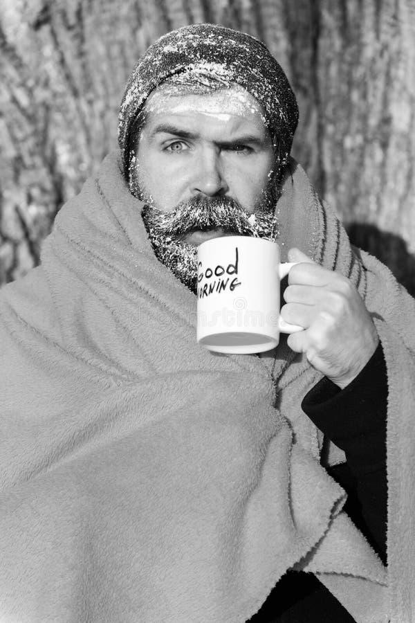 Замороженный удивленный человек, бородатый хипстер, с бородой и усиком покрытыми с белым заморозком и оранжевым одеялом с греть стоковое изображение