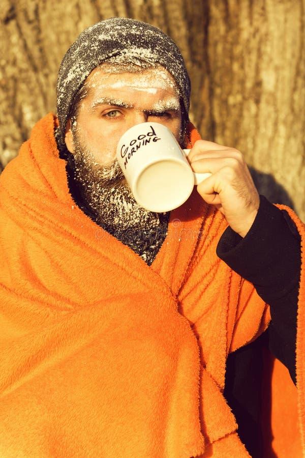 Замороженный человек, бородатый битник, при борода и усик предусматриванные с белым заморозком обернутые в оранжевом одеяле с гре стоковые фотографии rf