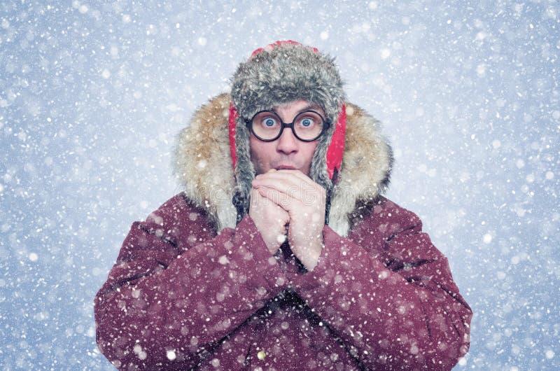 Замороженный человек в зиме одевает грея руки, холод, снег, вьюгу стоковое фото