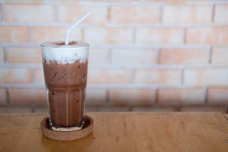Замороженный шоколад в высокорослом стекле с пеной парного молока на верхней части стоковое изображение